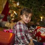 Alma sitter bland julklappar och ler