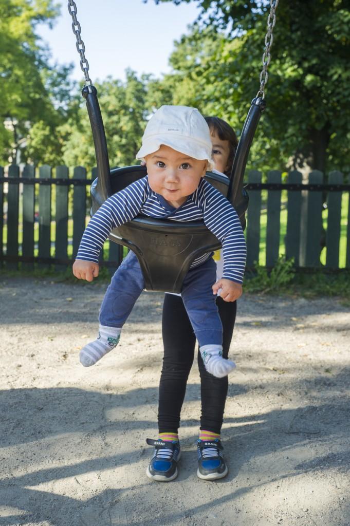 Alvin gungar och Alma knuffar på i parken